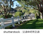 country road with white fence... | Shutterstock . vector #1184459218