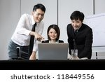 Chinese business team working together around a laptop - stock photo