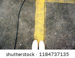 standing on the yellow line on... | Shutterstock . vector #1184737135