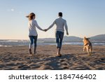 couple running on the beach... | Shutterstock . vector #1184746402