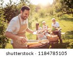 happy family having barbecue... | Shutterstock . vector #1184785105