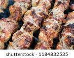 frying pork on a skewer over a...   Shutterstock . vector #1184832535