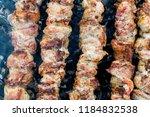 frying pork on a skewer over a...   Shutterstock . vector #1184832538