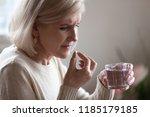upset senior ill woman holding... | Shutterstock . vector #1185179185