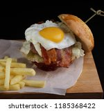 a large burger with scrambled...   Shutterstock . vector #1185368422