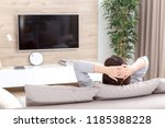young woman watching tv in the... | Shutterstock . vector #1185388228