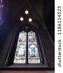 Small photo of Cambridge, England - March 13, 2014: A set of colourful stained glass window in geometrical stoned frame. An inside shot.