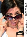 Small photo of Pretty Italian woman with sunglasses sticks out her tongue cheekily
