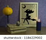 Small photo of Halloween pumpkin. The book of arcane magic. Frame and burning candle.