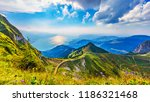Scenic summer panorama from Rochers de Naye mountain peak with green grassy hills, flower meadows and Geneva Lake in Alps, Switzerland