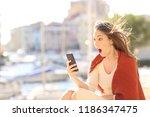 amazed woman watching on line... | Shutterstock . vector #1186347475