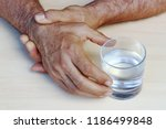 Small photo of The hands of a man with Parkinson's disease tremble. Strongly trembling hands of an older man