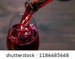 pouring red wine into the glass ... | Shutterstock . vector #1186685668