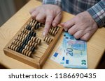 euro money and wooden calculator | Shutterstock . vector #1186690435