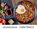 Small photo of Sweet and savory korean Japchae: bouncy cellophane noodles with mixed crunchy vegetables: spinach, red bell pepper, onion, carrot, garlic, shiitake mushrooms and beef with fried egg on top, flat lay