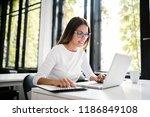 beautiful young woman analyzing ... | Shutterstock . vector #1186849108