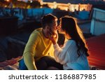 Stock photo loving couple is sitting on the roof of the house in the distance the lights of the night city 1186887985
