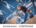 Steel House Constructor Worker. Caucasian Worker with Power Tool on the Building Frame. - stock photo