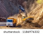 Small photo of Excavator is loading excavation to the truck. Excavators (hydraulic) are heavy construction equipment consisting of a boom, dipper (or stick), bucket and cab on a rotating platform.