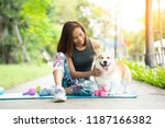 Stock photo a healthy woman playing with a corgi puppy while excersing on yoga mat surrounding with gym tools 1187166382