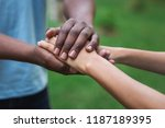Small photo of Black caregiver supporting woman, holding her hand outdoors. Philanthropy, kindness, volunteering concept, copy space