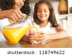 Mother Pouring Fresh Orange...
