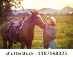 woman with her horse in evening ... | Shutterstock . vector #1187568325