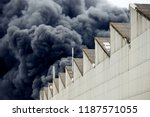 Small photo of Black plumes of smoke from an accidental toxic industrial fire as seen from a behind a factory building.