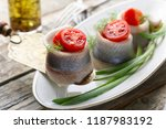 Stock photo herring rolls with dill green onion and cherry tomatoes on a old wooden table 1187983192