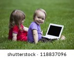 Little boy and girl using a little Laptop while sitting on meadow. The black space on the laptop could be used for any logos, some label signs or any graphic additions. - stock photo