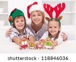 Happy woman with kids in christmas hats holding gingerbread people - stock photo