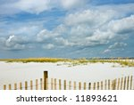 Beach, sea oats and big blue sky with sand fence in the foreground. Selective focus. Good background for ads, etc.