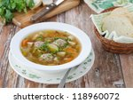 Plate of vegetable soup with meatballs on the wooden table - stock photo