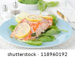 Baked salmon fillet with lemon and spinach on a plate - stock photo