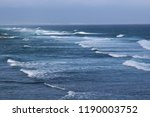 Small photo of Waves of the Pacific Ocean rolling in while surfers paddle out at Hookipa Beach in Paia, Maui, USA on a hazy day