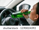 a driver holding alcoholic... | Shutterstock . vector #1190024392