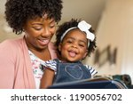 mother reading a book to her... | Shutterstock . vector #1190056702