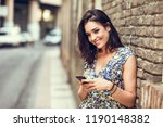 smiling young woman using her... | Shutterstock . vector #1190148382