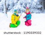 kids making snowman in snowy... | Shutterstock . vector #1190339332