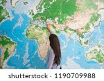 Woman from behind pointing on world map, geography