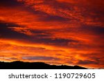 New Zealand Sunset showing fiery red sky and silhouette of hills