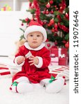 Cute baby girl in front of christmas tree wearing santa outfit - stock photo