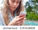 young girl using a phone | Shutterstock . vector #1191618838