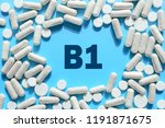 Small photo of Vitamin B1 text in white capsules frame on blue background. Pill with thiamine, thiamin. Dietary supplements and medication