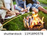 Several campers holding sticks with marshmellows over campfire while sitting around it