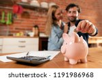 happy couple inserting coin in... | Shutterstock . vector #1191986968