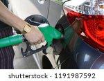 man fills petrol into her car... | Shutterstock . vector #1191987592