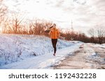 woman running at snowy mountain. | Shutterstock . vector #1192432228