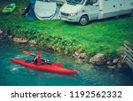 Waterfront RV and Tent Camping with Kayaking. Caucasian Sportsman in the Kayak on Glacial Lake. - stock photo