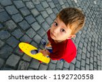little boy on skateboard looks... | Shutterstock . vector #1192720558